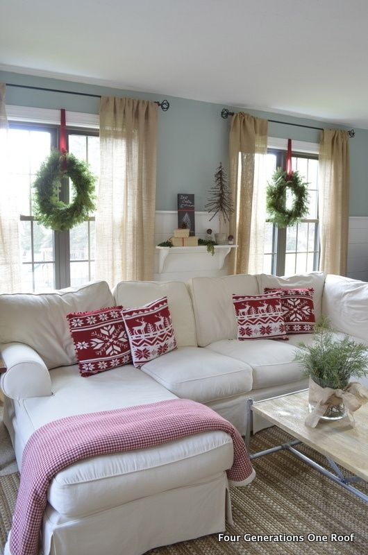 A Pretty Red And White Christmas Living Room With Green Wreaths On The Windows Love Idea Of Using Ribbon To Hang I Couch