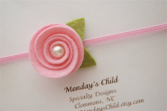 This sweet headband is made with wool blend felt with a pearl cabochon center! The little flower and leafs measure 1.5 inches and are attached to