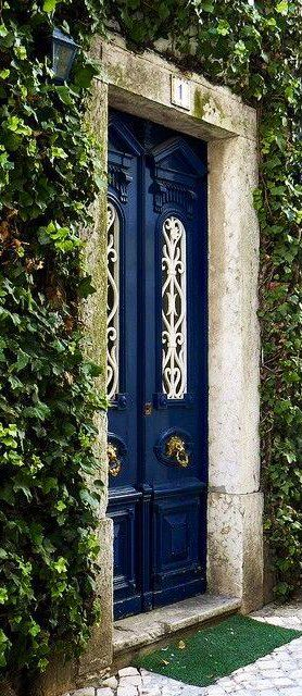 rich blue door surrounded by ivy growing up the house