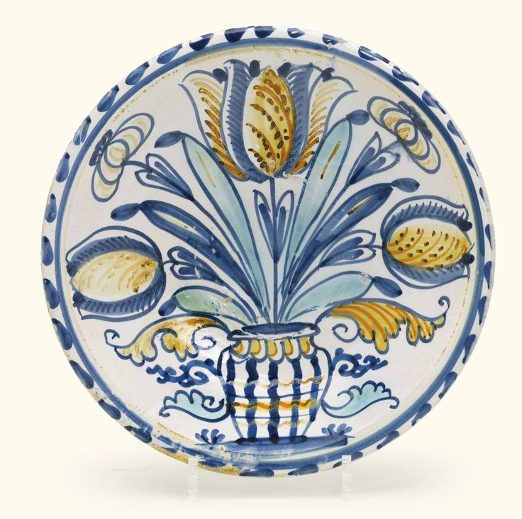 Sold @ Sotheby's A Brislington delftware blue-dash tulip charger, circa 1685-1705 painted in blue, ochre and turquoise with tulips and lilies standing in a striped vase flanked by scrolling leaves