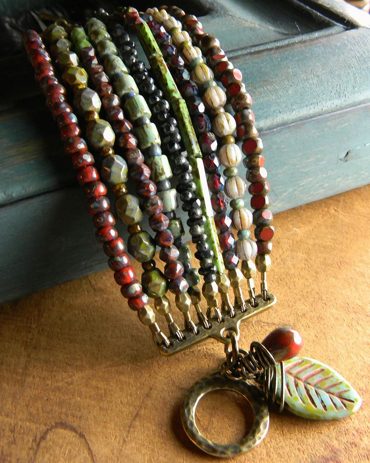 Colorful, but in a subdued kind of way, nine strands of beautiful Picasso Czech glass in assorted shapes and small sizes. The bead colors range from soft gray green to brick red and ruddy sienna. Each strand has a faceted antique brass bead on the ends, giving it a rustic but finished look that blends with the Tierra Cast toggle clasp. I designed this bracelet to be small, so it fits snugly on a 6 inch wrist. If you need additional length, please send me a message.