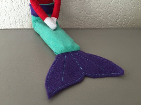Even elves dream of being mermaids! This prop is made to make mermaid and merman dreams come true! Each tail measures about 10 long and about 3 wide. Tails are handmade with flannel and felt and have detail stitched into the fin! Color Options (updated May 4, 2016)! From left to right, Pink with purple fins, Aqua with purple fins, Light Pink with pink fins, Light Blue with pink fins, Green with blue fins, Blue with aqua fins, and Hot Pink with glitter navy fins. Limited amounts available…