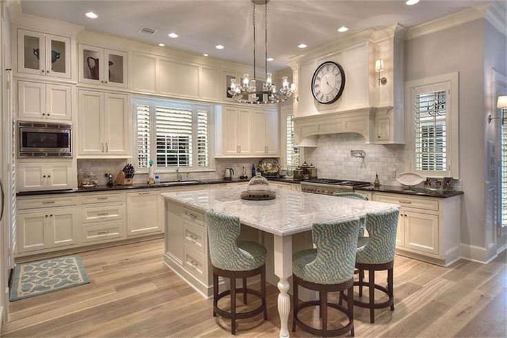 Absolutely stunning Kitchen with large marble-top island, lots of windows w/plantation shutters, high ceilings, custom marble backsplash, custom venthood, B/I pot filler, state of the art SS appliances, gorgeous chandelier, & glass-front upper cabs.