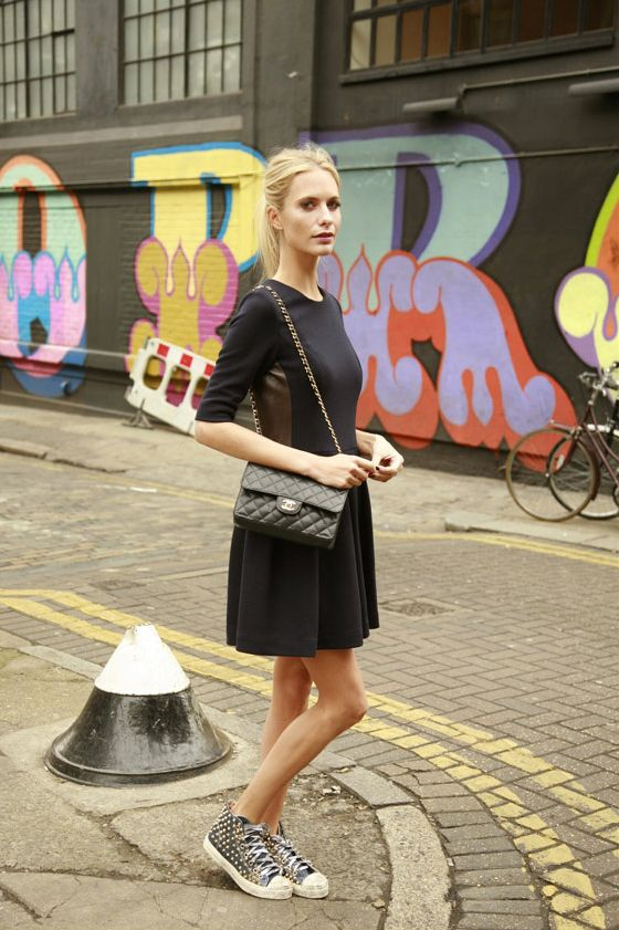 Poppy Delevigne pairs her little black dress with a classic Chanel bag and a pair of studded sneakers.  VOGUE.ES