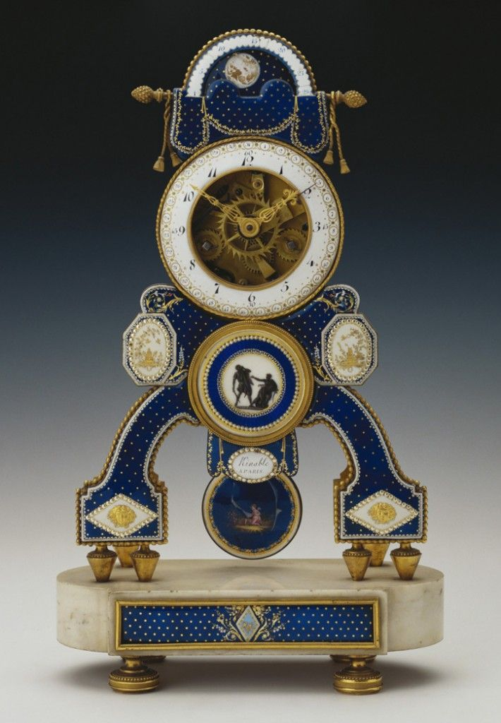 Skeleton Clock Royal Collection - A mantel 'skeleton' clock with porcelain plaques by the Royal manufactory of Sèvres has applied gilt bronze ornaments and a dial enameled with signs of the Zodiac. It was made by French clockmaker Dieudonné Kinable & is rendered in gilded metal. It has also been enameled on the front in blue and white with spots, lozenges and pearlized dots, similar to that appeared for a short time on Sévres porcelain of the 1780's.