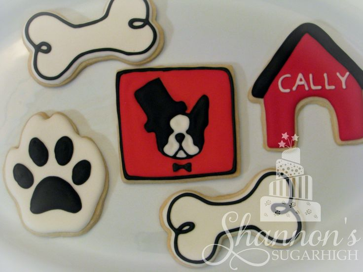 Boston Terrier theme royal icing painted shortbread cookies in black, white, and red. Set includes dog houses with dog's name, bones, paws, and dog faces with bowties and top hats. Boston Terrier face cookie made to match the design from the party invitation found on www.smooshfaceunited.com . Keyword: Sugar cookie.
