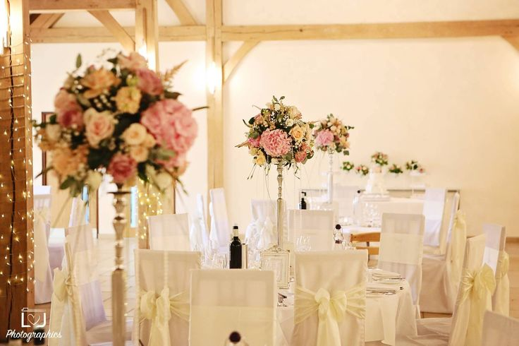 Tall centrepieces at Rivervale Barn using shades of pink and blush with hanging crystals on silver candle stands by www.tarniawilliams.co.uk