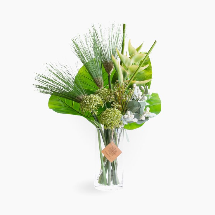 Contemporary artificial flower arrangement using tropical flowers and foliage including heliconia, cyperus, tetragona nuts, allium and calla leaves.