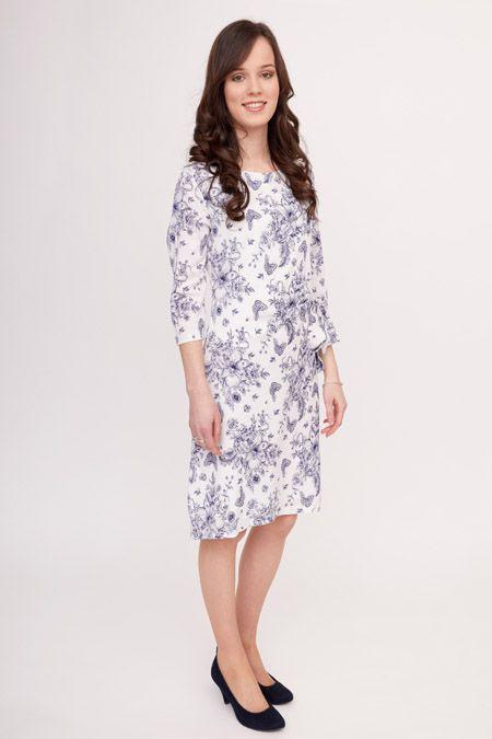 Dit witte jurkje met delfts-blauw achtige print is gemaakt van een stof met linnen-kwaliteit. Het ontwerp heeft een plooi op de linkerheup, waaraan ook een ceintuur zit vastgestikt.