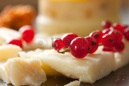 Closeup shot of cheese and redcurrant, selective focus. Stock Photo