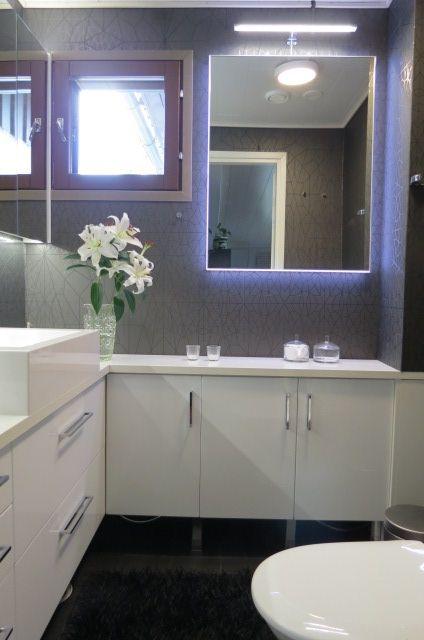 Seesteinen tunnelma wc:hen on saatu aikaan yhdistelmällä kirkkaanvalkoista ja tummanharmaata .