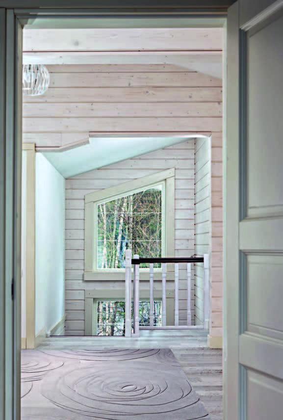 Благодаря тому, что гостиная представляет собой двусветное пространство, из холла второго этажа открывается вид на лесной пейзаж.