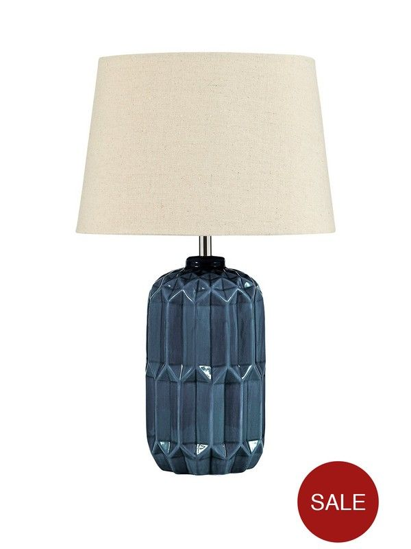 Naples Table Lamp – 44cm Give your space a little Mediterranean flavor with this eye-catching table lamp. Available in 2 glossy colours – red and blue – the faceted texture of the base gives it a sense of depth that's enhanced wonderfully as light escaping from the beige shade is reflected in different directions.Depth: 28 CMHeight: 44 CMWidth: 28 CM