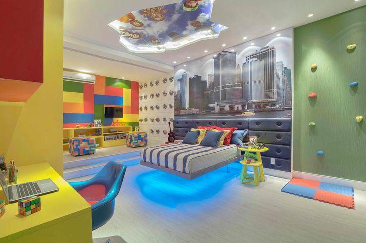 As peças de Lego são a cara da infância e, por isso, são a inspiração de Ana Cecília Lima e Patrícia Matos. O colorido está na parede de escalada, nas pinturas dos painéis, nos móveis fixos. A cama chama a atenção, com pés de acrílico e iluminação RGB que muda de cor, além de cabeceira em jeans. Outro detalhe é o teto recortado que mostra uma historinha.