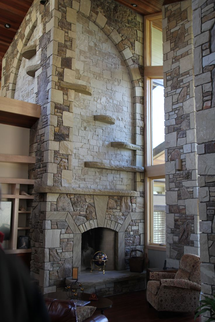 Extravagant fireplace steals the show stone fireplace for the spacious - An Impressive Stone Fireplace Graces The Interior Of The River Home The Fine Details Of The Stone Arch And Stone Ledges Give The Fireplace A Commanding