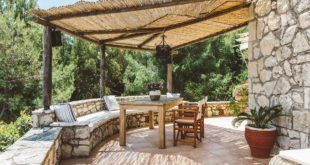 GREEK STYLE VILLAS - Breakfast table on the shaded terrace with a bamboo roof.