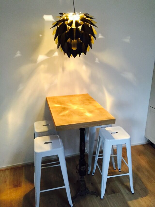 Keukentafel van eikenhout gemaakt door de Kleine Industrie, witte metalen barkrukken en een shiny lamp. Hoppa