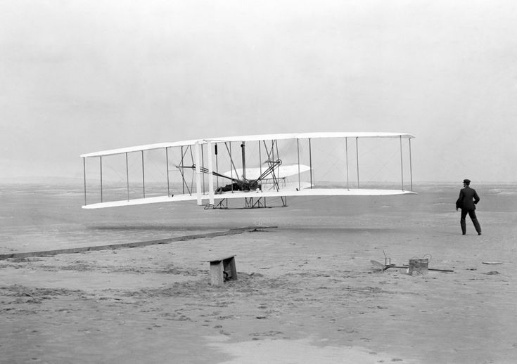 Dec. 17, 1903 — Flight at Kitty Hawk. In this 1903 picture taken in Kitty Hawk, North Carolina, Orville Wright is seen manning the controls on the lower wing, piloting the Wright Flyer on the first powered flight ever. In the moments before the plane was airborne, his brother, Wilbur Wright, on the ground, guided and steadied the plane as it accelerated along the starting rail at left.