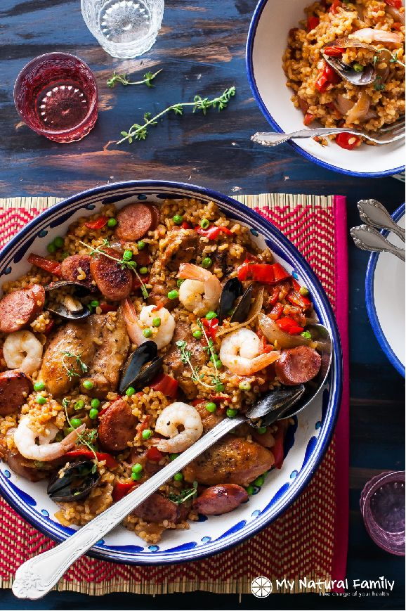 A clean eating paella and rice recipe with chicken thighs, shrimp, mussels, and turkey sausage (chorizo?) links. It is full of vegetables and flavor!
