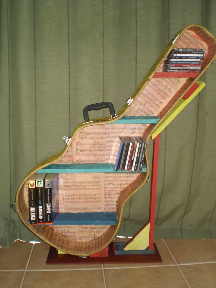 A guitar case re-purposed into a CD/Book shelf. Decoupage old news paper on the outside and sheet music on inside. Designed to be wall mounted but I made a stand until then