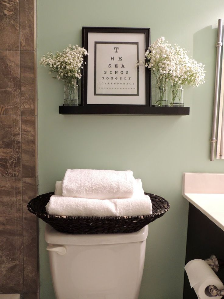 Floating shelf for above toilet with a framed quote, mason jars, and flowers.