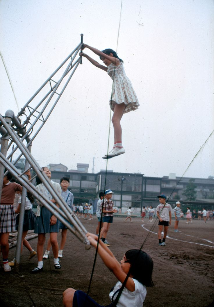 A school girl soars twice her height in a standing version of a seesaw in Tokyo, Japan, November 1964.Photograph by Winfield Parks, National Geographic