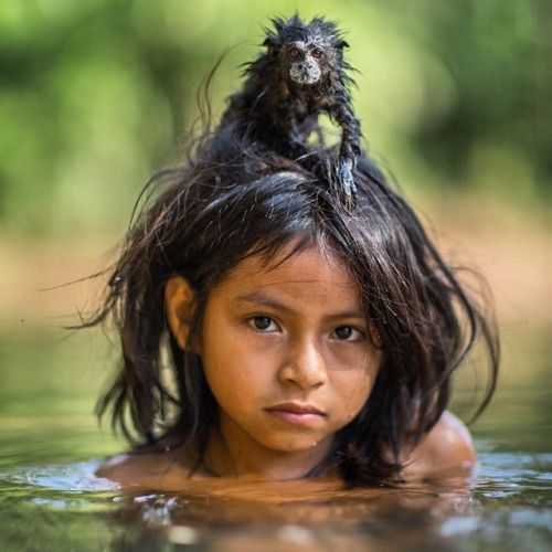 Yoina, a 9 year old girl of the Machiguenga community from the Peruvian Amazon, with her pet Saddle-back Tamarin