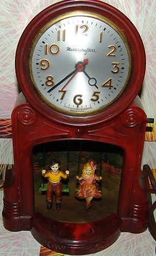 vintage clock with bakelite boy and girl swinging