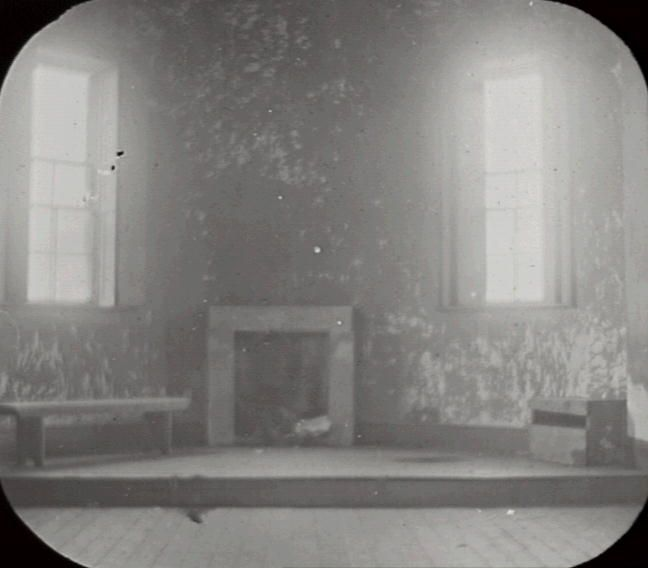 Title: Interior, Hartley Court House Date & Location: 27 July 1912, Hartley (NSW); Lithgow (NSW) Description: Black and white glass lantern slide. Title in ink on upper edge label. Notes: View of interior of dilapidated Grecian Revival courthouse at Hartley, showing dais with fireplace on wall of apse, flanked by windows, with wooden floorboards in foreground. Designed by colonial architect Mortimer Lewis. From negative in Mitchell Library Frank Walker Collection ON 150, Item 954.