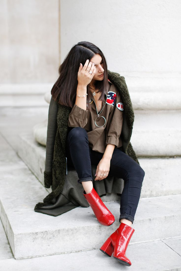 Anisa Sojka styles army green Zara shearling coat | Embroidered patch top with silver zip | Gold and silver PANDORA jewellery | Stacked vintage and timeless elegance rings | Locket necklace with Celestial Petites charms | Shiny red ankle boots | Fashion blogger street style shot in London by Victoria Metaxas