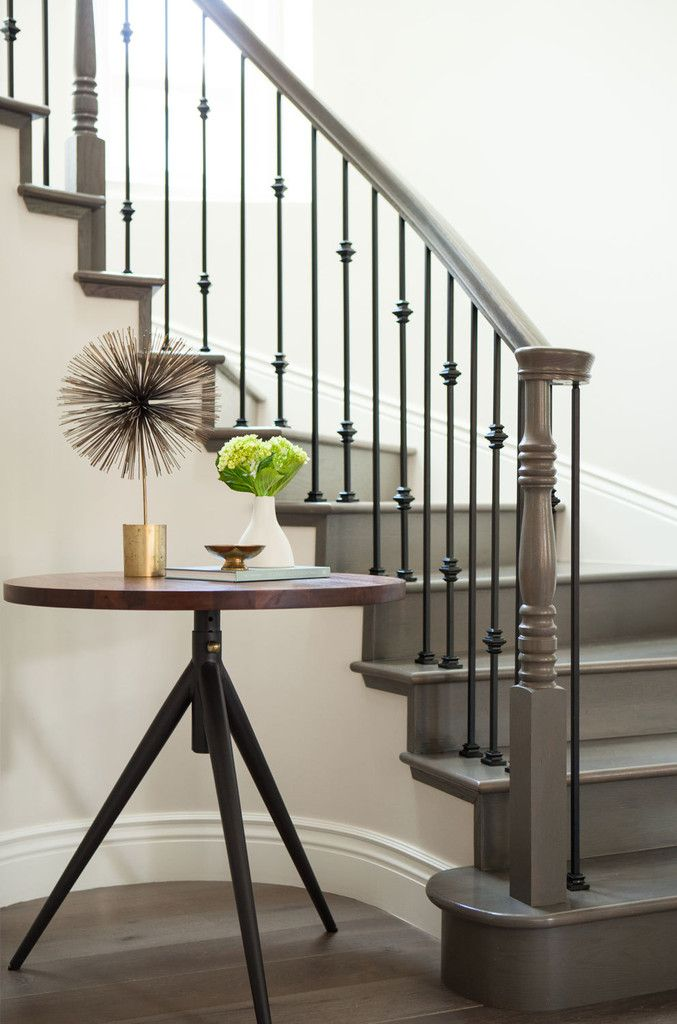 The home's original staircase curves up and around a three-legged table from West Elm.