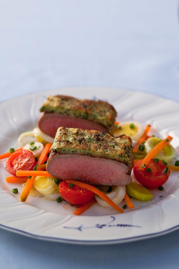 Köstliches Lamm Rezept mit feiner Kräuterkruste aus Frischkäse und mit Gemüse serviert.