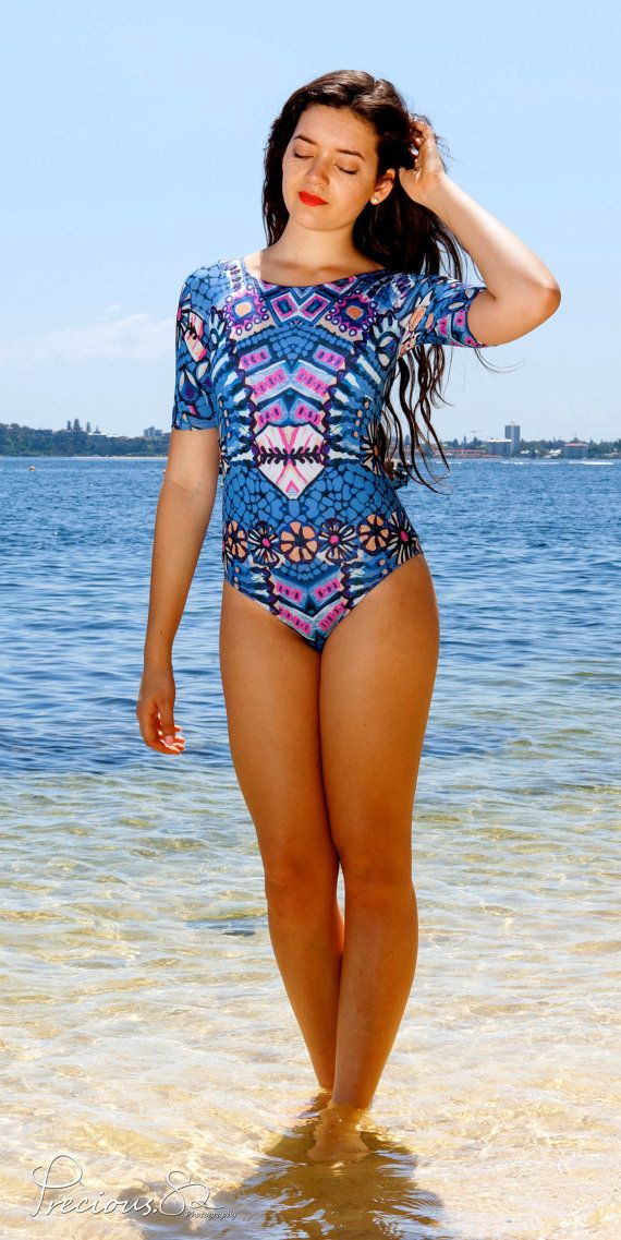 Shine On Me One Piece Swimsuit with Short Sleeves, Scoop Neck and Classic Leg in Majestic Print Stand out in Style with this elegant bodysuit.