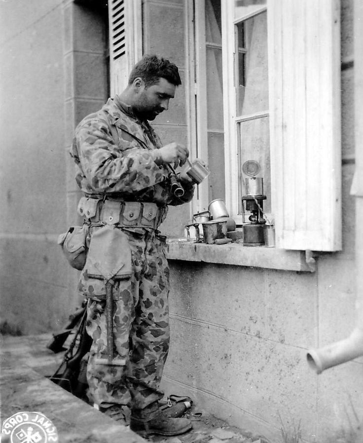 Le Private Joseph G. De Freitas de Yonkers (New-York) d'un Antitank Platoon, 41st Armored Infantry Regiment de la 2nd US Armored Division fait chauffer les boîtes de ses rations sur son réchaud individuel. Photo prise le 28 juillet 1944 au Pont-Brocard, hameau de Dongy (Manche), point de passage sur la Soulles