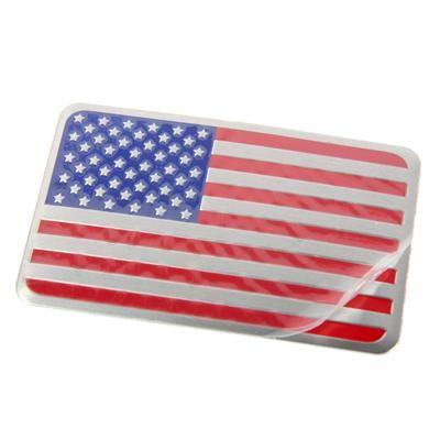 Stars & Stripes Emblem. Emblem i aluminium med det amerikanske flag præget i overfladen.  8 cm bred og 5 cm høj og 1,5 mm tyk.  Beskyttelsesfolie på forsiden og selvklæbende bagside.