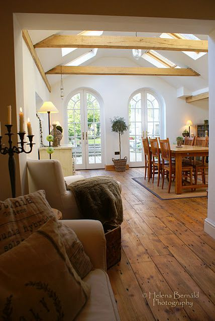 Plank wood floors, arched french doors and wood beam ceiling with natural light.