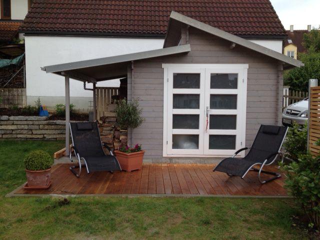 Pultdach Gartenhaus in Hellgrau und Weiß. Auf der Naturholzterrasse kann man sich gemütlich im Liegestuhl sonnen.