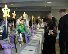 Elevated item identifiers! Easy way to remember items of interest or what was bid on. No more crouching to stare at tables to find items.  Celebration guests study item descriptins at the silent auction table.