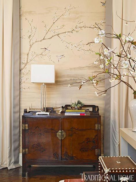An antique chest lends Asian flair to this corner of the dining room. A hand-painted mural lies behind cream-and-gray draperies - Traditional Home® / Photo: Emily Followill / Designer: Melanie Turner