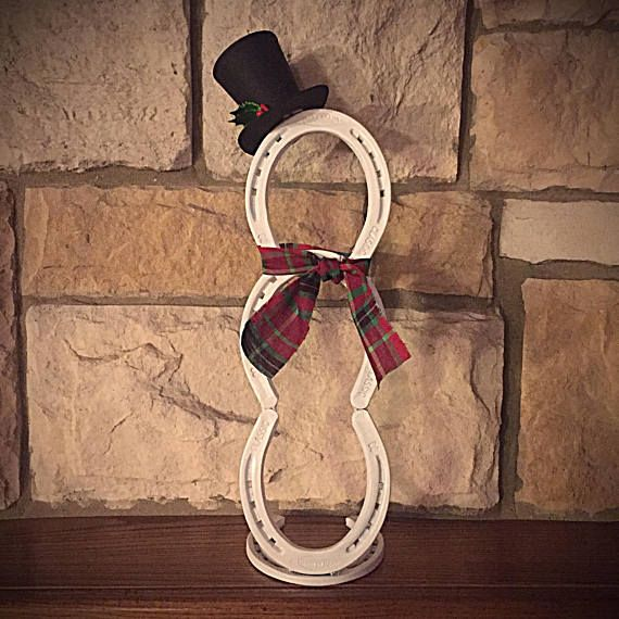 Horse Shoe Snowman Hand made snowman made with 4 used horse shoes that have been cleaned, welded and painted white. They stand approximately 16 inches tall. The hat is hand painted black with holly glued to it. The hat is removable so to allow for safer storage. A 2 inch piece of a horse shoe has been welded on top of the head to hold the hat in place. If there are any customization that you would prefer (i.e. scarf print, shoe or hat color) please let us know. Only shipping within the U.S…