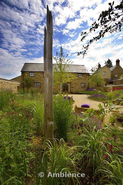 Rickyard Barn giardino, Northamptonshire - vista dal retro del giardino ghiaia alla casa con la scultura legni, Trifolium Rubens, muro rosso, sedili rock e cuscini viola