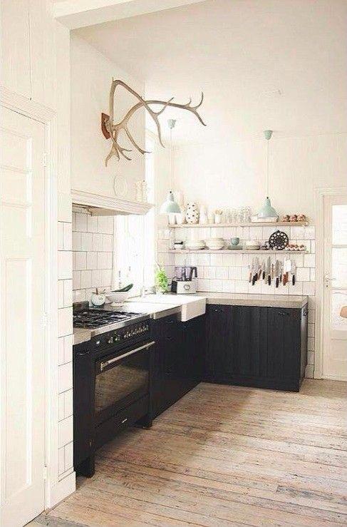 Verona stove || Fantastic Frank, L-Shaped Kitchen in Sweden, unfinished wood floors, open wood shelves, white subway tiles | Remodelista