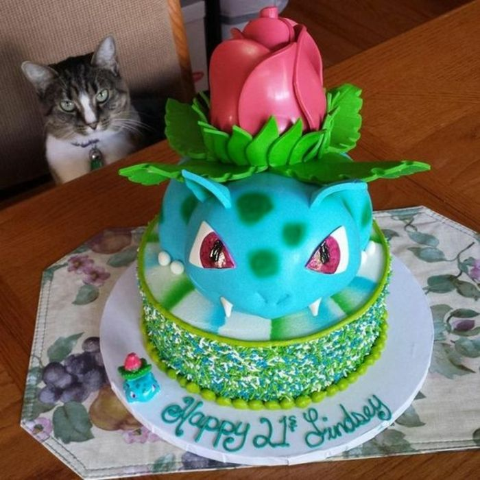 hier ist eine katze mit einer blauen pokemon torte mit einem blauen pokemon wesen und einer schönen, roten. großen rose und ein weißer teller