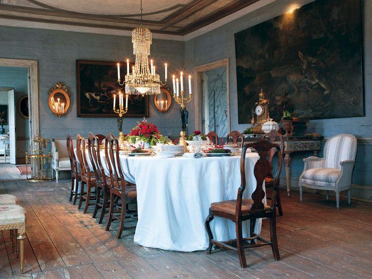En stor matsal på herrgården med middagsbord och antika stolar.