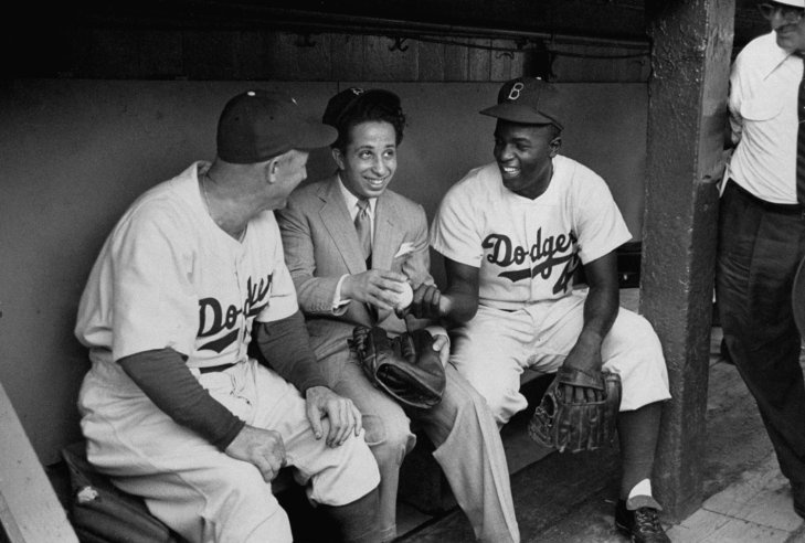 Brooklyn manager Charlie Dressen, Iraq's 17-year old King Faisal II (invited to the US by President Truman) and Jackie Robinson chat in the Dodger dugout in 1952.
