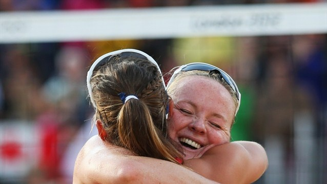 Zara Dampney and Shauna Mullin of Great Britain celebrate victory after the women's Beach Volleyball preliminary match between Great Britain and Canada on Day 2 of the London 2012 Olympic Games at Horse Guards Parade.