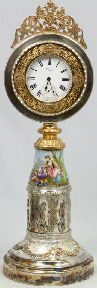 """Clock Hourglass Time:  Antique Russian Pavel Buhre #pocket #watch set in Russian silver and enamel guilloche presentation mounting. Watch has white enamel face with black Roman numerals and notches. Mounting has raised floral ribbon design throughout with chase work base. Has hand painted enameled scene depicting mother and child in countryside landscape scene. Holds 1893 assayer's mark with 84 silver purity mark and town mark. Measures 10 3/4"""" height (27.3cm)..."""