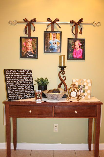 Use a curtain rod, tie pictures to it using ribbon.