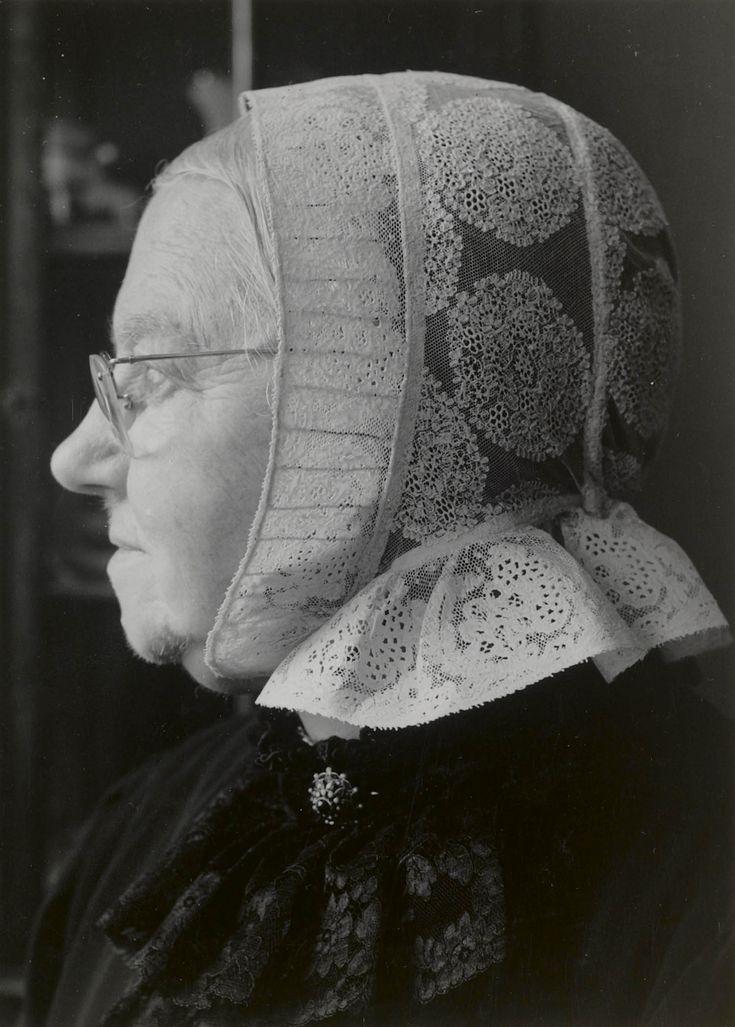 Mevrouw Risseeuw-Tromp in Cadzandse streekdracht. Mevrouw Risseeuw woont in Middelburg en was 80 jaar op het moment dat de foto werd gemaakt. Ze draagt een schootjak met rok en een schortje met broderie-borduursel. Op het jak draagt ze een zwart kanten jabot. Onder de kanten cornetmuts draagt ze een zwarte ondermuts met mutsenbellen, die nog juist zichtbaar zijn in de voorstrook van de cornetmuts (ter hoogte van de mond). #Cadzand