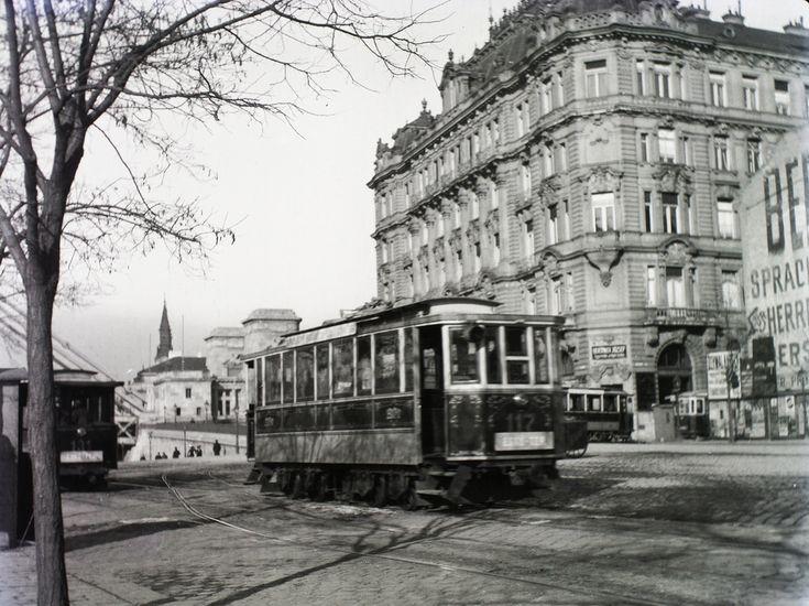 Villamosok suhannak a mai Belgrád rakparton, a távolban az Erzsébet híd és az ortodox templom tornya a Petőfi téren. Az Irányi utca sarkán még csak egy tűzfal van az 1911-ben emelt ház helyén, de az 1903-ban épített bérház már áll. (Fotó: Schmidt Albin / Fortepan)